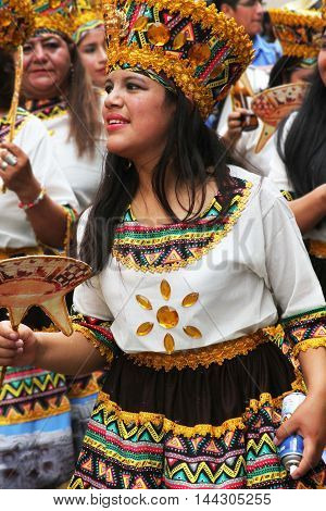 Cajamarca Peru - February 7 2016: Close up of smiling young woman in headdress and traditional costume marching in Carnival parade in Cajamarca Peru on February 7 2016