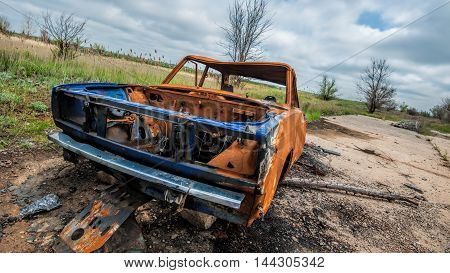 Rusty burned wrecked car in steppe near Volgograd