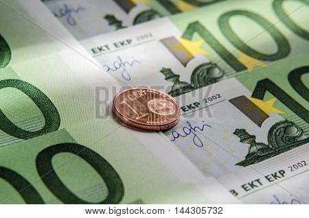 100 Euro banknotes and coin of one cent. Macro. Background.