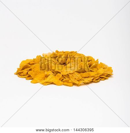 Pile of corn flakes against a white backdrop.