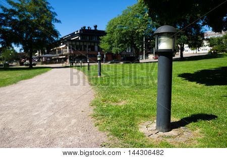 Lamp by a walkway in a park on a beautiful summer day.