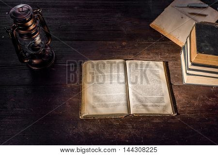 Old-fashioned kerosene lamp and opened book on the dark table in twilight. Soft focus