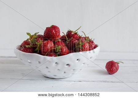 white ceramic colander with strawberries strawberry in a clay colander strawberries on white background.