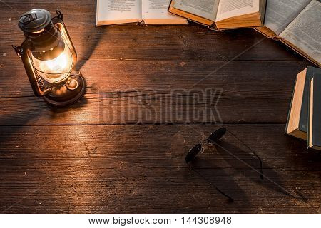 Old-fashioned kerosene lamp and opened books on the dark table in twilight. Soft focus