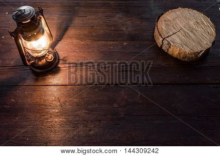 Thin saw cut of spruce wood and old-fashioned kerosene lamp on the dark table in twilight. Soft focus