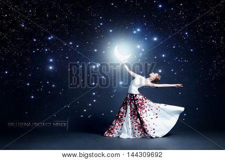Young ballerina in a beautiful dress is dancing in a dark photostudio