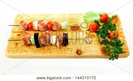 Pieces of raw pork and vegetables on grill stick on wooden board over white background