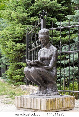 Modern park sculptures: Sitting girl reading a book