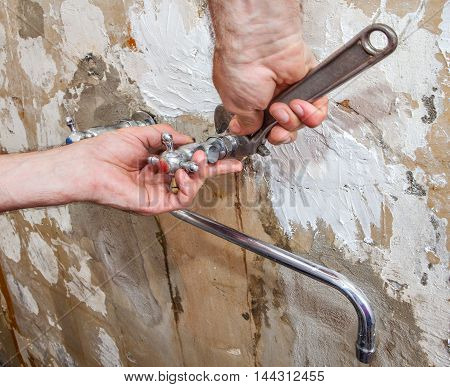 Dismantling of old faulty faucet close-up hands of plumber with adjustable wrench.