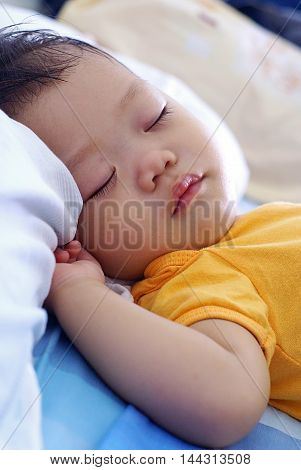 Cute Asian infant baby in orange dress is sleeping on the bed.