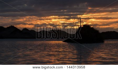 Black cross on a island with a setting sun going into storm clouds.