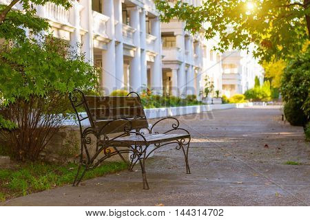 Street forged bench is in green Park on territory of departmental sanatorium Raduga. On background is white building of hospital with concrete columns. Sochi Krasnodarskiy kray Russia