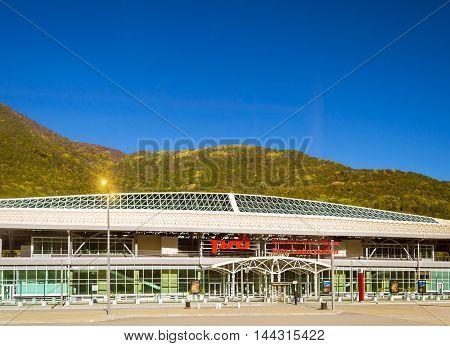 SOCHI RUSSIA - OCTOBER 31 2015: Railway Esto-Sadok station on the backdrop of the Caucasus mountains and blue sky. Logo of Russian Railways on facade. Krasnaya Polyana Sochi Krasnodarskiy kray Russia