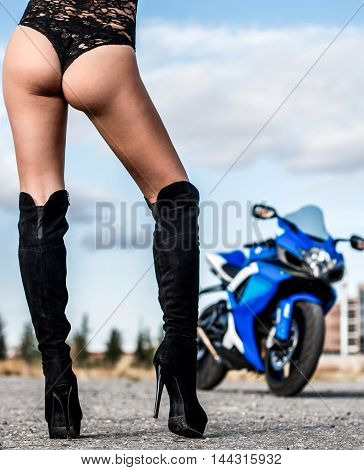 Fit female legs at the background of the blue bike