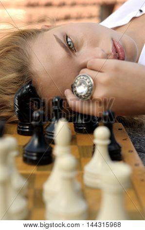 Woman Lies Near The Chess Board