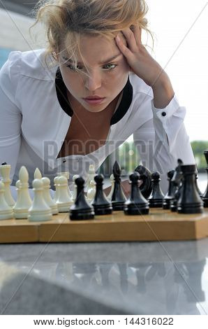 Woman Playing Chess Outdoors.