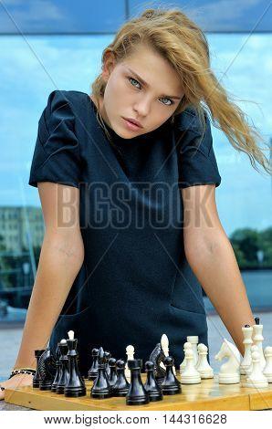 Girl Stands Near A Chessboard