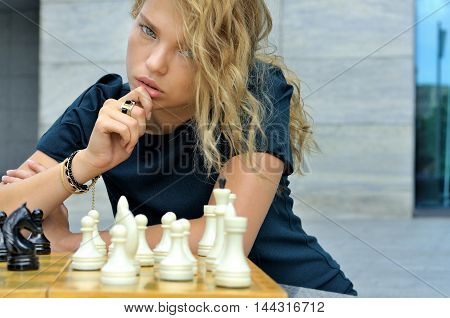 Girl Thinks How To Make A Move On The Chessboard