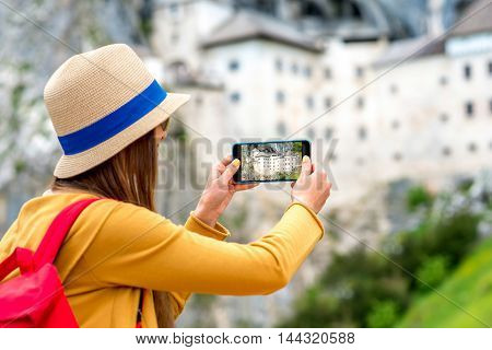 Young female traveler photographing with phone Predjama castle. This castle is a famous tourist attraction and a travel destination in Slovenia