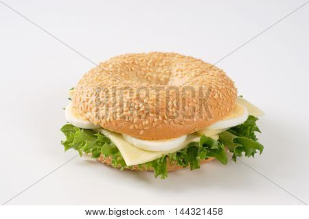 bagel sandwich with eggs and cheese on white background