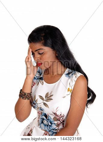 An beautiful Indian woman with long black hair sitting and holding her head for a headache isolated for white background.