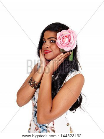 A beautiful smiling Indian woman with long black hair holding a pink rose to her face isolated for white background.