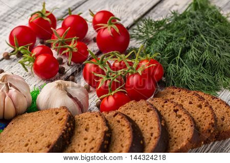 Still life on wooden background: tomatoes black bread garlic fennel bayberry pepper