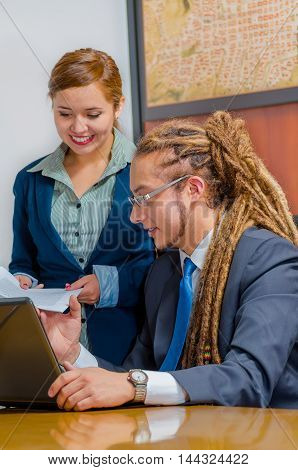 Handsome young man wearing formal suit sitting down with pretty female co-worker standing beside him looking at screen and discussing between each other, office manager concept.