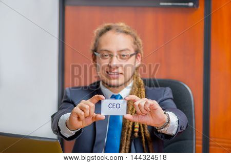Handsome man with dreads, glasses and business suit sitting by desk holding up a paper which has the word executive written on it in his pocket, young manager concept.