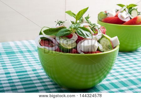 Green Bowl With Vegetable Salad  On A Green Checkered Tablecloth