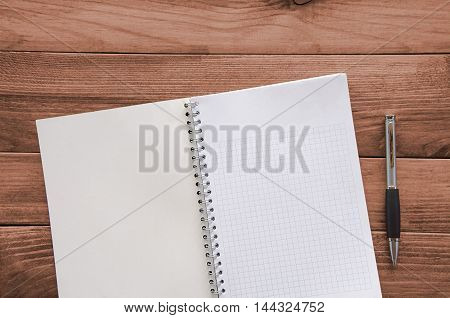 White sheet paper with pen for text on wooden table