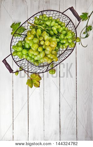 Fresh green grapes in vintage basket with vine and leaves on wooden board rustic style
