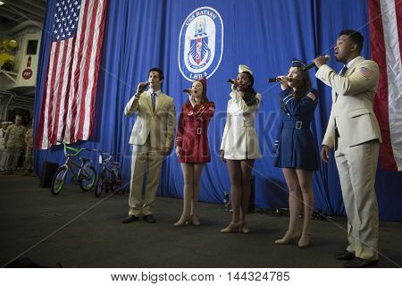 NEW YORK MAY 26 2016: USO Show Troupe pose/perform under the American Flag in the hangar bay of the amphibious assault ship USS Bataan (LDH 5) during the USO Build-A-Bike event during Fleet Week 2016.