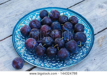 Freshly picked plums in a pretty dish on a picnic table.