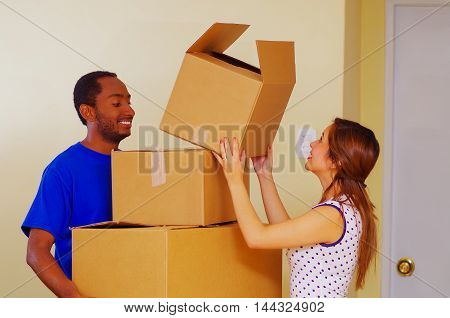 Charming interracial couple smiling and interacting while stacking cardboard boxes, moving in concept.