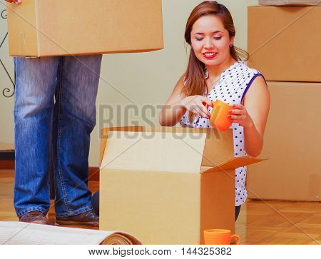 Charming interracial couple working together, woman sitting down unpacking cardboard box while smiling, man standing behind with only legs visible, moving in concept.