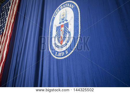 NEW YORK MAY 26 2016: The insignia of the amphibious assault ship USS Bataan (LDH 5) on a large blue curtain hanging in the hangar bay during the USO Build-A-Bike event during Fleet Week 2016.