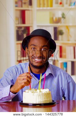 Charming man wearing blue shirt and hat sitting by table with birthday cake in front, touching candle celebrating alone smiling.
