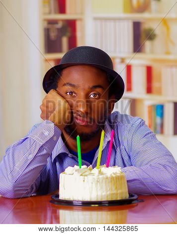 Charming man wearing blue shirt and hat sitting by table with birthday cake in front, looking sad depressed celebrating alone.