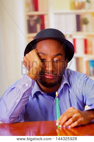 Charming man wearing blue shirt and hat sitting by table with one candle looking depressed, celebrating alone.
