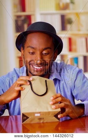 Charming man wearing blue shirt and hat sitting by table opening birthday present, looking happily excited, celebrating alone concept.