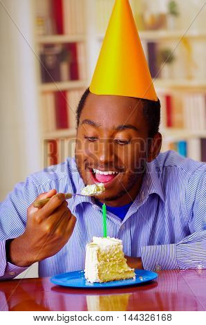 Charming man wearing blue shirt and hat sitting by table eating piece of cake in front, looking happy, celebrating alone concept.