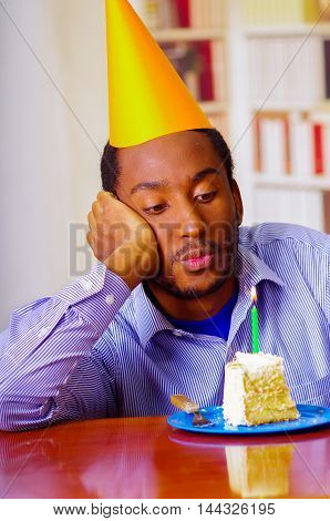 Thoughtful man wearing blue shirt and hat sitting by table with piece of cake in front, looking sad, celebrating alone concept.