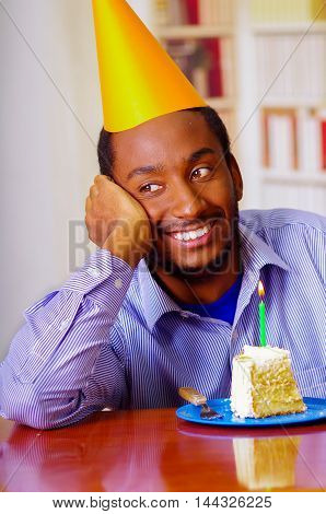 Charming man wearing blue shirt and hat sitting by table with piece of cake in front, looking happy, celebrating alone concept.