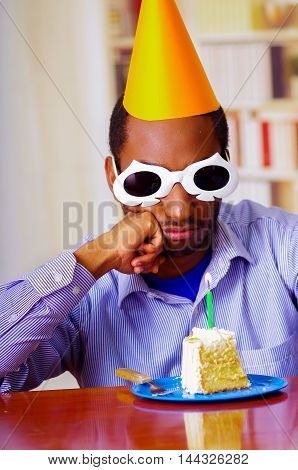 Good looking man wearing blue shirt, white spectacular sunglasses and yellow party hat sitting by table staring at piece of cake in front, celebrating alone concept.