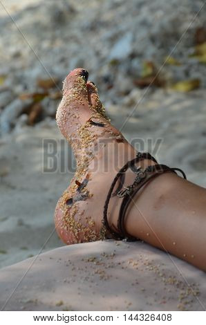 the sandy foot of a woman that relaxes on the beach