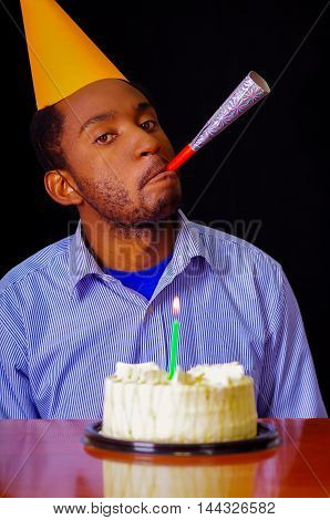 Good looking man wearing blue shirt and hat sitting by table with cake in front, single candle burning, blowing party horn facing camera, celebrating alone concept.