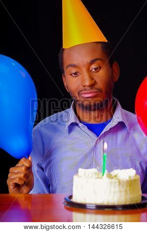 Good looking man wearing blue shirt and hat sitting by table with cake in front, single candle burning, holding balloons facing camera, celebrating alone concept.