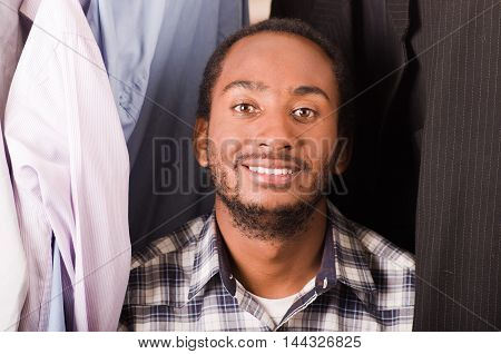 Headshot handsome young man standing inside wardrobe with clothes sorrounding, smiling to camera.