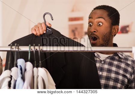 Handsome young man standing inside wardrobe going through rack of different clothes hanging, fashion concept.